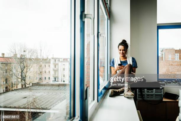 Young casual businesswoman with smart phone sitting on window sill