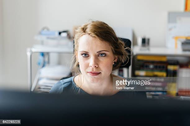 young casual businesswoman working at computer - determination stock pictures, royalty-free photos & images