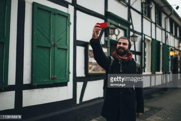 joven hombre vestido casual con teléfono inteligente en la calle de la ciudad - dortmund ciudad fotografías e imágenes de stock