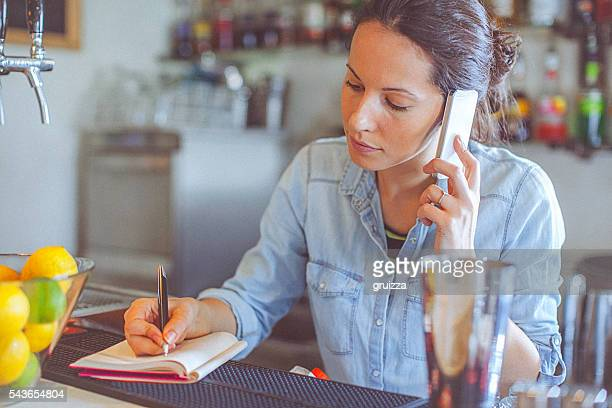 Young, casual female bar owner ordering merchandise