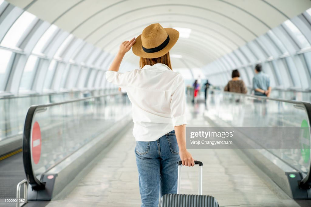 Young casual female traveler with suitcase at airport : Stockfoto