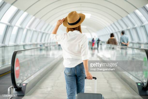 young casual female traveler with suitcase at airport - travel stock pictures, royalty-free photos & images