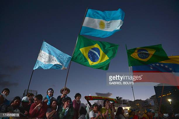 Young Catholic pilgrims attending World Youth Day wave flags of Argentina Brazil and Venezuela as they wait for the arrival of Pope Francis for a...