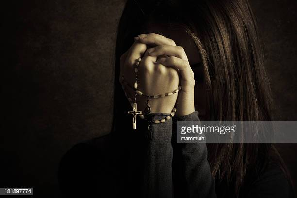 Young catholic woman praying with rosary