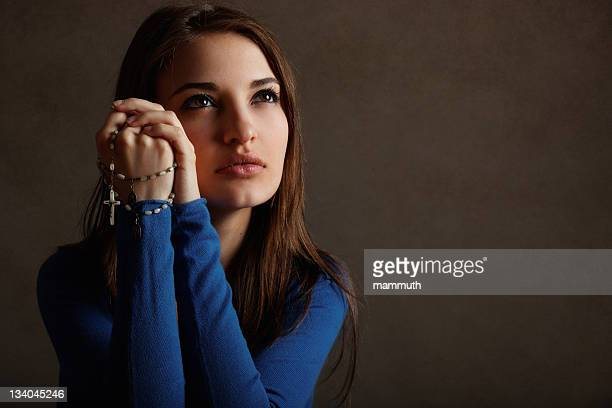 Young catholic woman prays with rosary
