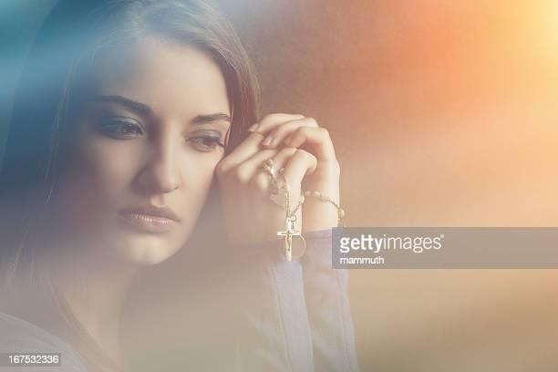Catholique jeune femme se recueille avec du Rosaire