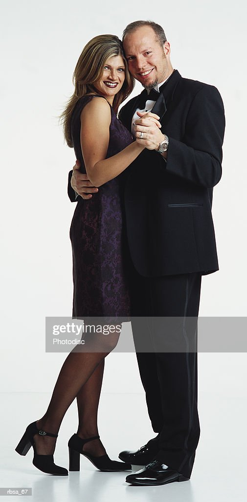 young caucasian adult blonde female wearing short purple silk sleeveless dress and heels standing in dance position with young caucasian adult balding male with facial hair wearing tuxedo looking as a couple at the camera and smiling : Foto de stock