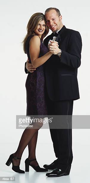 young caucasian adult blonde female wearing short purple silk sleeveless dress and heels standing in dance position with young caucasian adult balding male with facial hair wearing tuxedo looking as a couple at the camera and smiling - evening wear stock pictures, royalty-free photos & images