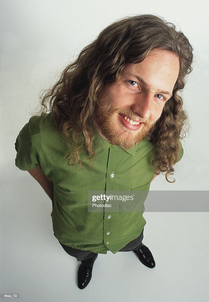 Young caucasian adult male hippie with facial hair and long curly hair wears a green shirt and stands looking up at the camera with a mischievous smile : Stockfoto