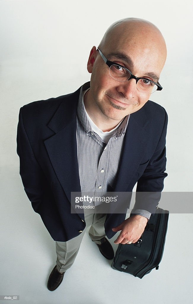 young caucasian bald man with glasses and a goatee in a blue blazer and tan pants with a checkered shirt looking up at the camera his arm leaning on a suitcase : Foto de stock