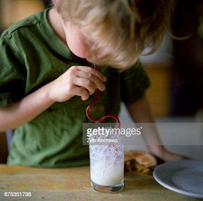 Young caucasian boy blowing milk bubbles