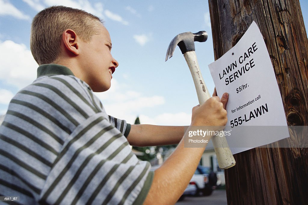 A young caucasian boy nails a lawn care sign on a telephone pole : Stockfoto