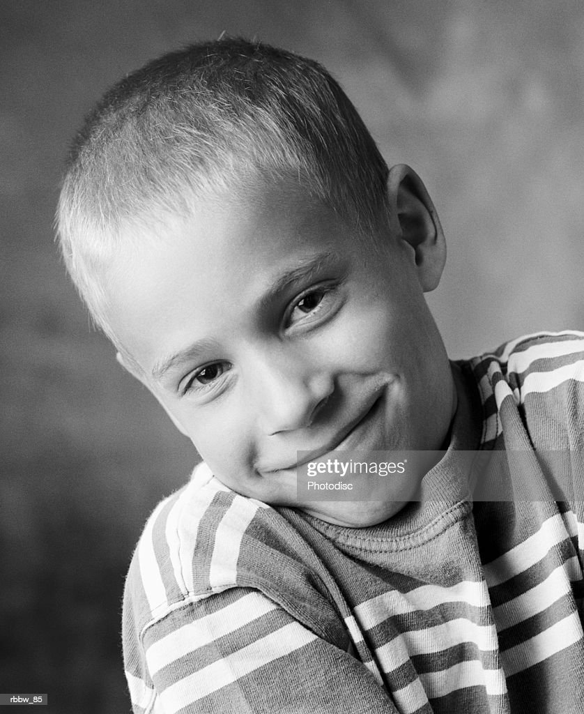 A young caucasian boy shrugs a sheepish grin : ストックフォト