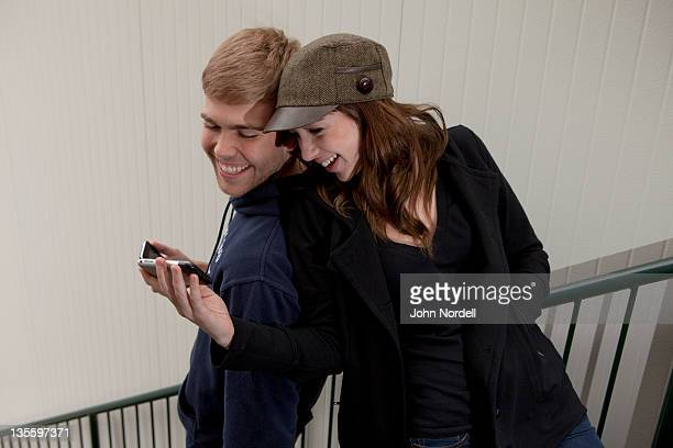 Young Caucasian couple, 20-21 years old, texting each other and friends