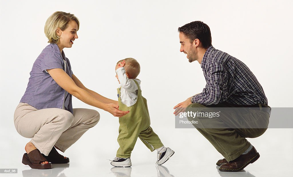 young caucasian couple kneel with baby in overalls who walks towards the mom : Stockfoto