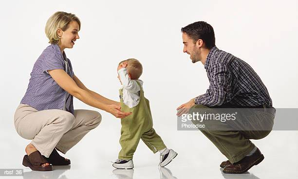 young caucasian couple kneel with baby in overalls who walks towards the mom