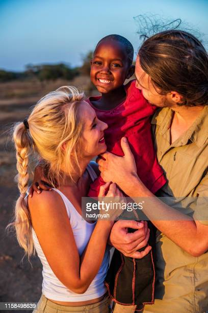 young caucasian couple posing with their black adopted daughter - east africa stock pictures, royalty-free photos & images