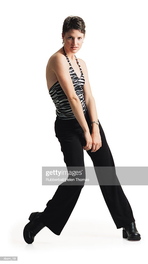young caucasian female dancer in black pants ans a zebra print tank top dances as she throws her shoulder forward : Foto de stock