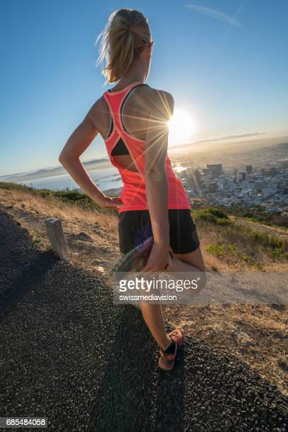 Young Caucasian female stretching muscles at sunrise