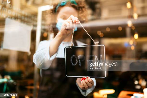 young caucasian female waitress reopening her cafe - reopening stock pictures, royalty-free photos & images