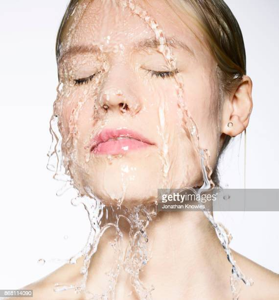 Young Caucasian female with water running down her face