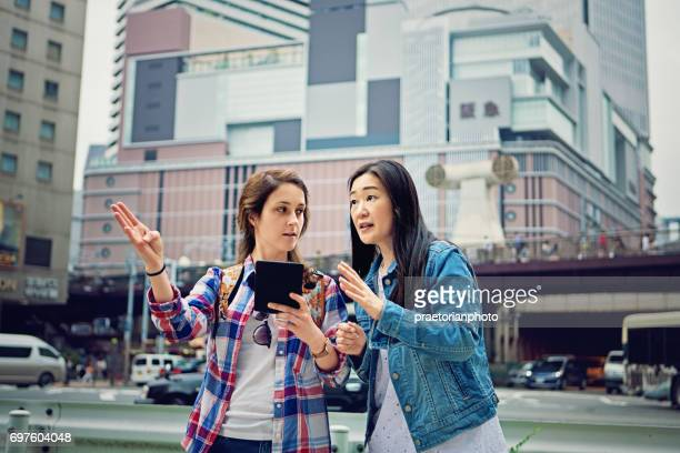 Young caucasian girl is lost in Japan and asking local mature woman for help