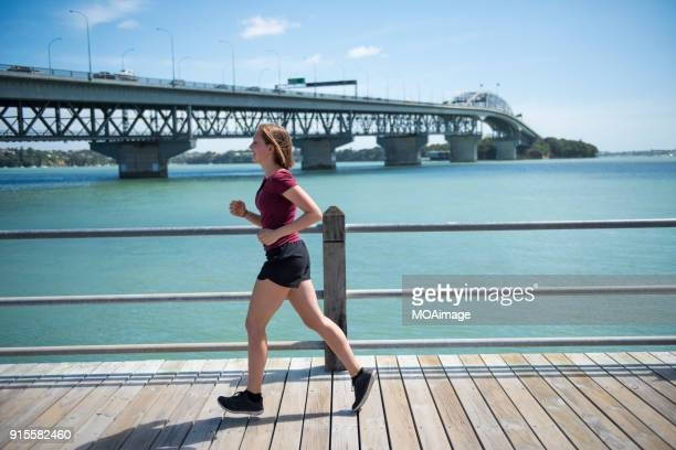 A young Caucasian girl is running at the Auckland seaside