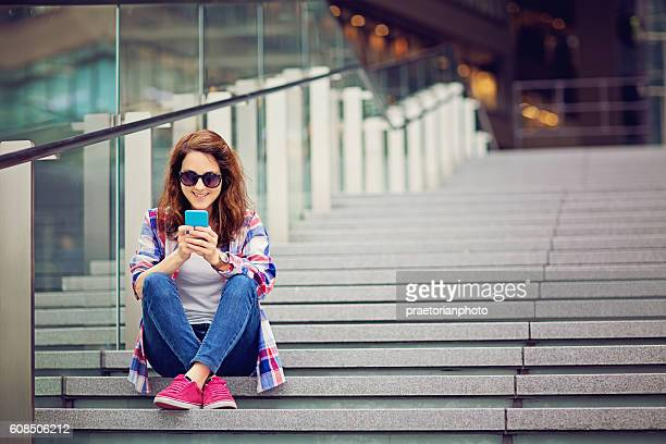 Young Caucasian girl is texting sitting on the stairs