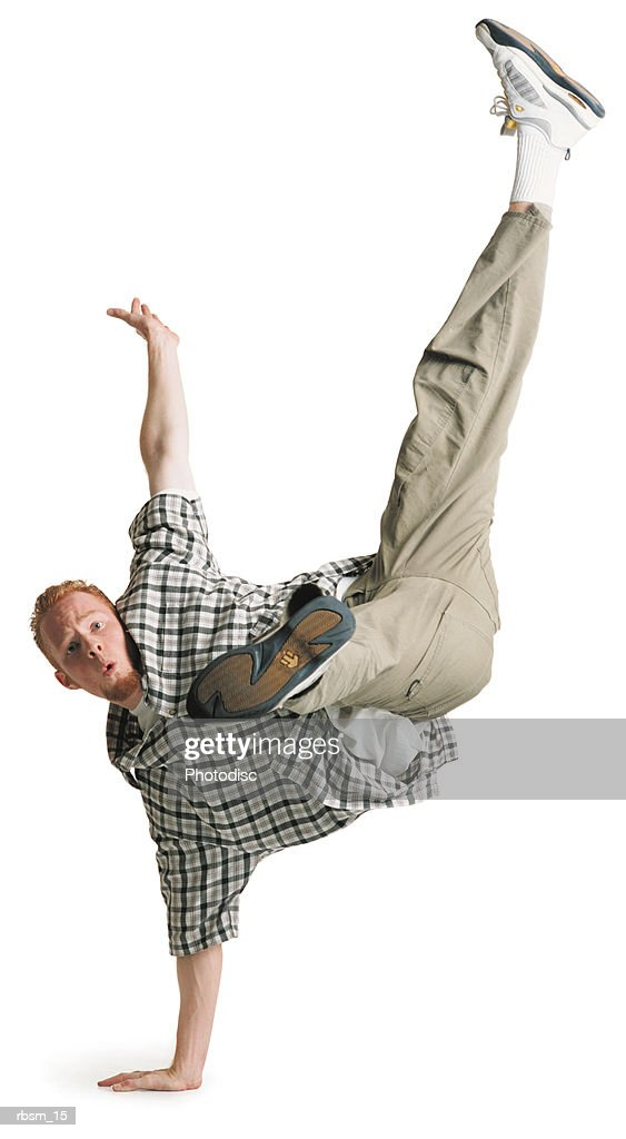 young caucasian male breakdancer in kakhi pants and plaid shirt kicks his legs in the air in the splits while balancing on one hand : Foto de stock