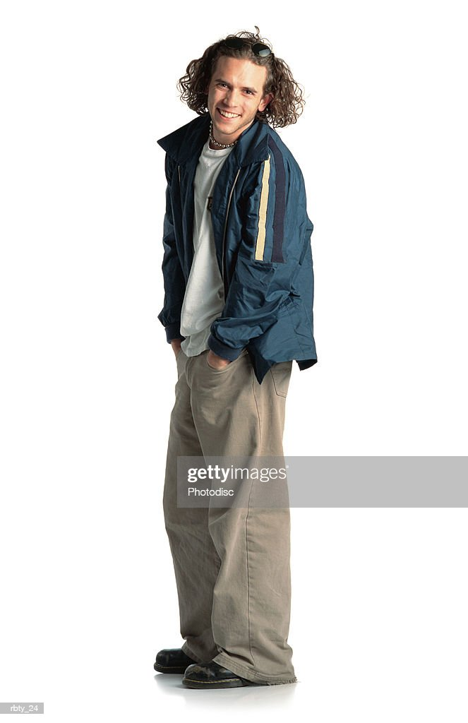 young caucasian male dressed in alternative clothing stands with his hands in his pockets as he turns to the right and smiles back at the camera : Foto de stock