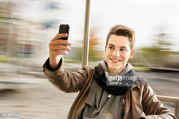 Young Caucasian male takes a selfie on a spinning carousel.