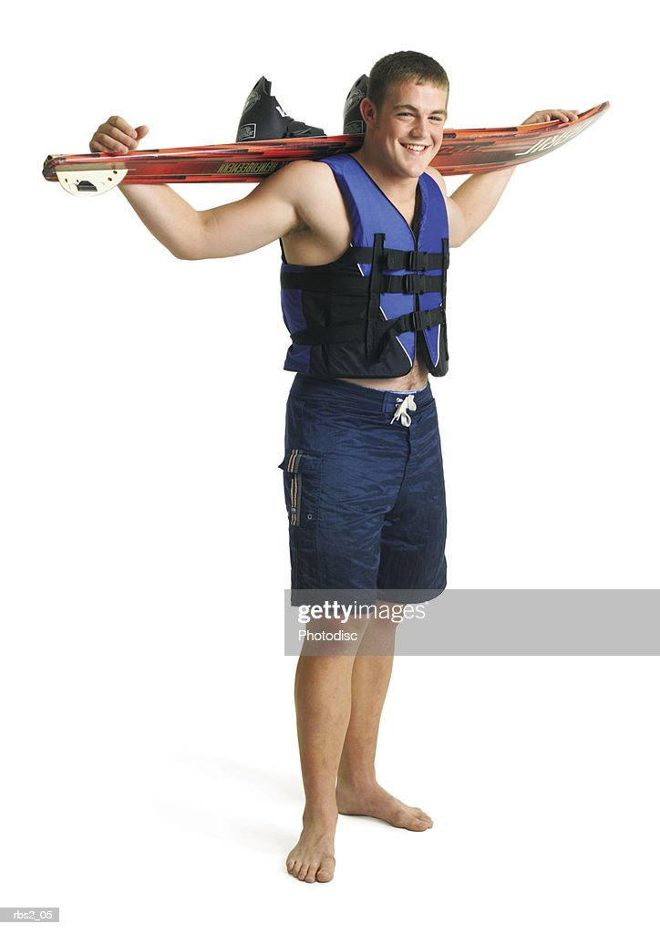 young caucasian male waterskier wears blue lifejacket swimsuit holds waterski over shoulders smiles : Foto de stock