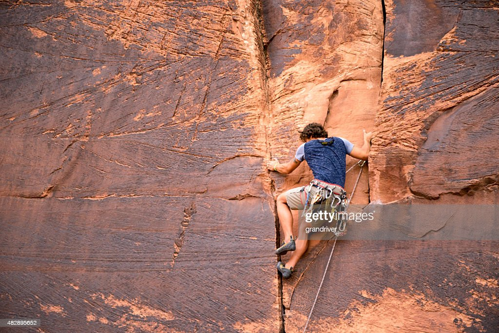 Young Caucasian Man Climbing a Sheer Cliff of Red Sandstone : Stock Photo