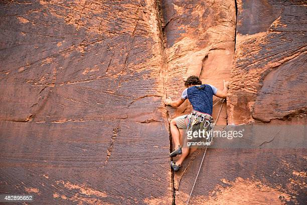 Young Caucasian Man Climbing a Sheer Cliff of Red Sandstone