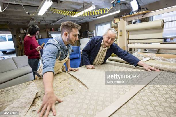 Young Caucasian man learning the art of upholstery from a senior male upholsterer.