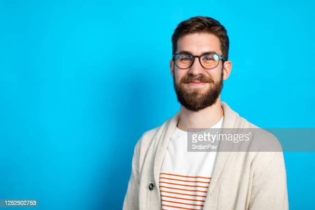 young caucasian man posing against blue background - coloured background stock pictures, royalty-free photos & images