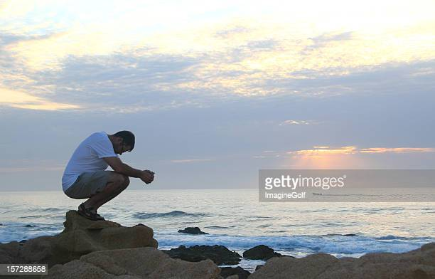 young caucasian man praying beside ocean - mexican god stock pictures, royalty-free photos & images