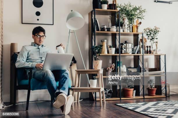 Kaukasische jongeman zit thuis en computer gebruikt voor surfen op het net