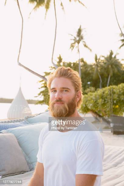 a young caucasian man sitting on a day bed by the beach during sunset - one man only stock pictures, royalty-free photos & images