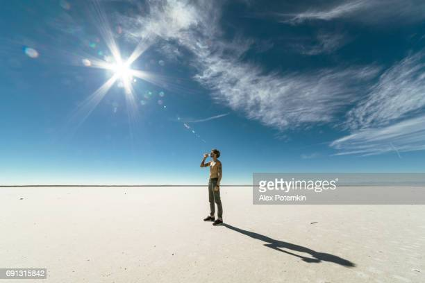 Young Caucasian man, thirsty hiker, drinking the water in the Salt Flats desert, Utah, USA