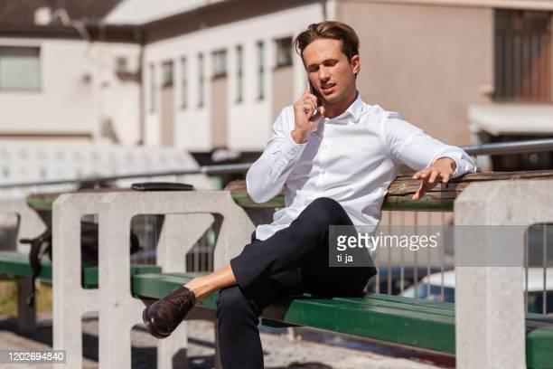 jeune homme caucasien utilisant le téléphone portable à l'extérieur photo de stock - décontracté chic photos et images de collection