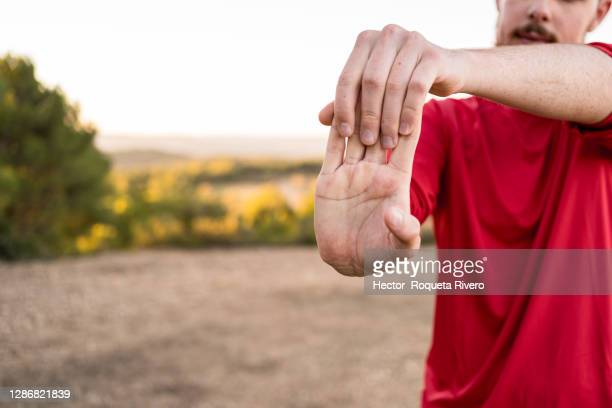 young caucasian man with beard, brown hair and red sportswear practicing sport exercise in the field. healthy life concept - hector vivas fotografías e imágenes de stock