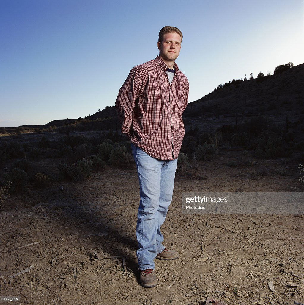 young caucasian man with jeans and red long sleeved shirt stands outdoors looking into the camera : Stockfoto
