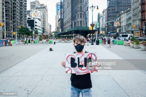"Young Caucasian protester holds up their homemade sign on a box that says, ""BLM"" with peace symbols all around it and stands in front of the Flat..."