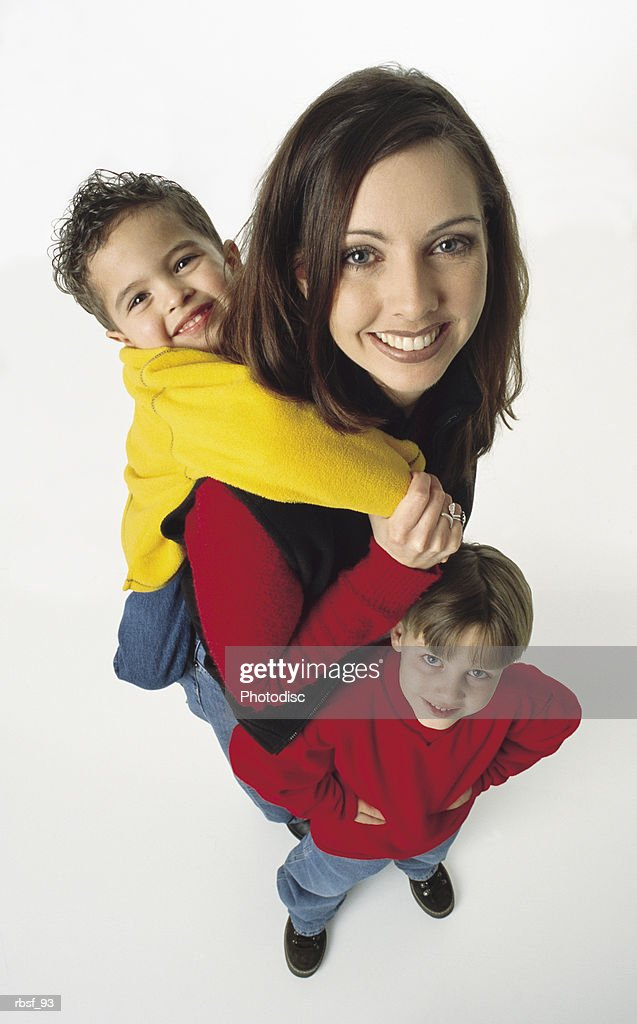 young caucasian single mom with one kid in yellow on her back and one kid in red with hands on hips standing next to her : Foto de stock
