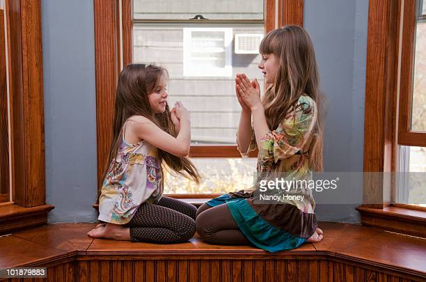 Young Caucasian sisters playing on a window sill