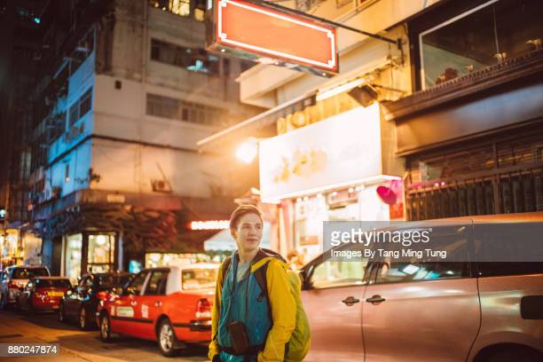 Young caucasian tourist in Hong Kong's street at night time.