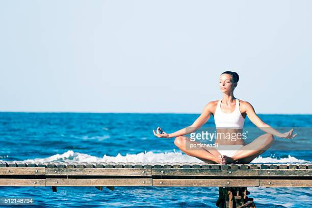 Young caucasian white woman doing yoga on the quay