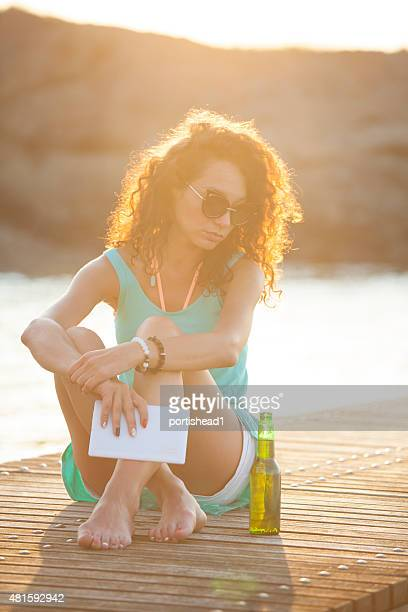 Junge kaukasischen weiße Frau sitzt auf den Kai