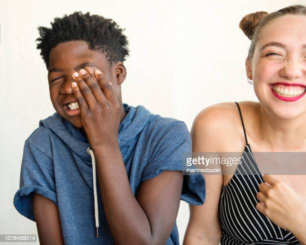 Young caucasian woman and african-american boy candid portrait.
